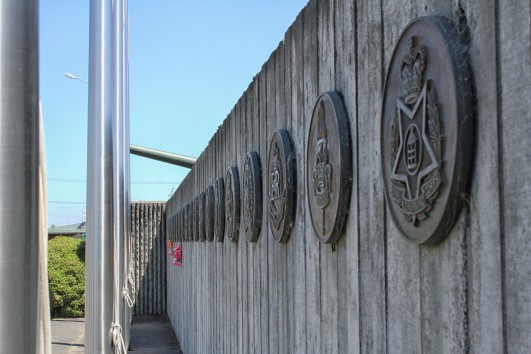 A memorial wall featuring NZ army unit and corps badges