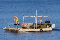 Strange barge-boat complete with trampoline, party lights, couches... and is that a pizza oven??