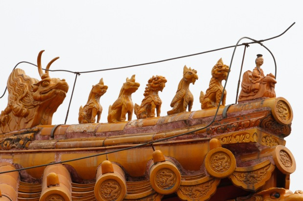 Imperial roof decorations were prevalent in the Forbidden City. At the front is a man riding a phoenix, at the back is a dragon, and in between are mythical beasts. Usually in odd number combos, the more beasts the more important the building. The maximum is 10 which only the Hall of Supreme Harmony has.