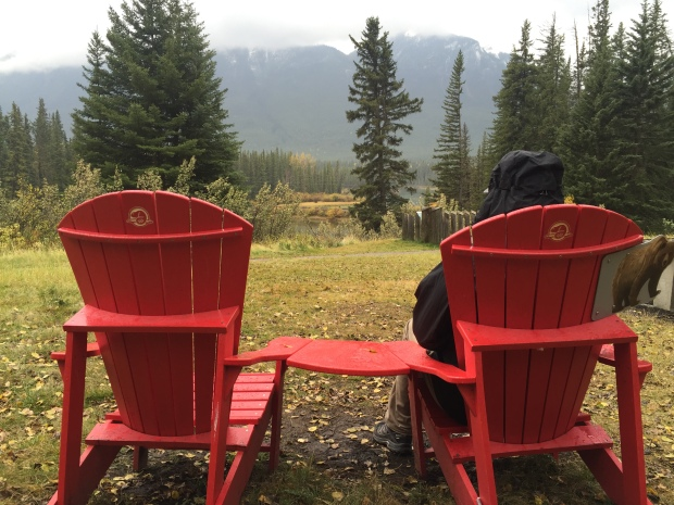 Red chairs in the woods at Mule Shoe Lake along the Bow Valley Parkway.